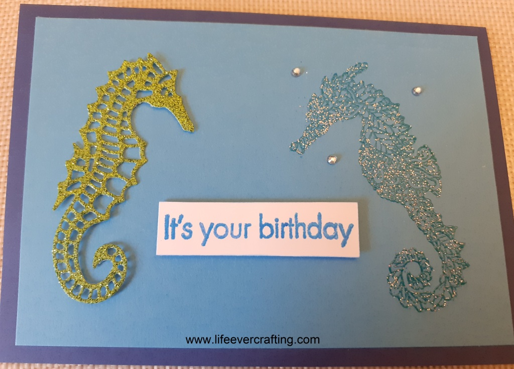 The image is of a blue card with two seahorses facing each other. The one on the left is cut from green glitter card and the one on the right is a glittery dark blue. There are three blue gem dotted around the head of the one on the right and there is a sentiment between them reading It's your birthday.