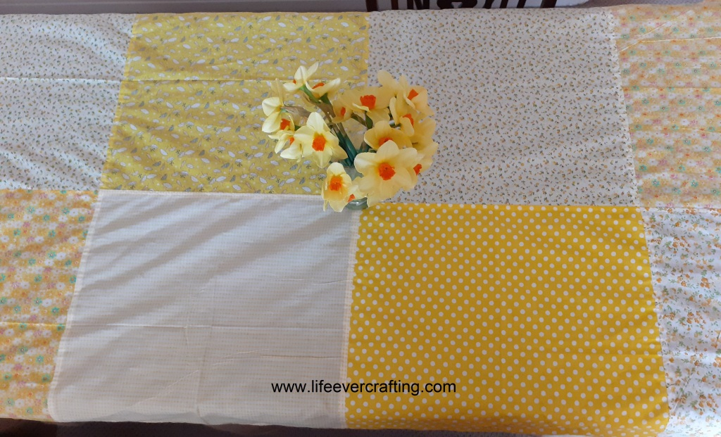 The image shows a yellow tablecloth made with the fat quarters shown before, with a a vase of daffodils in the centre of the table.