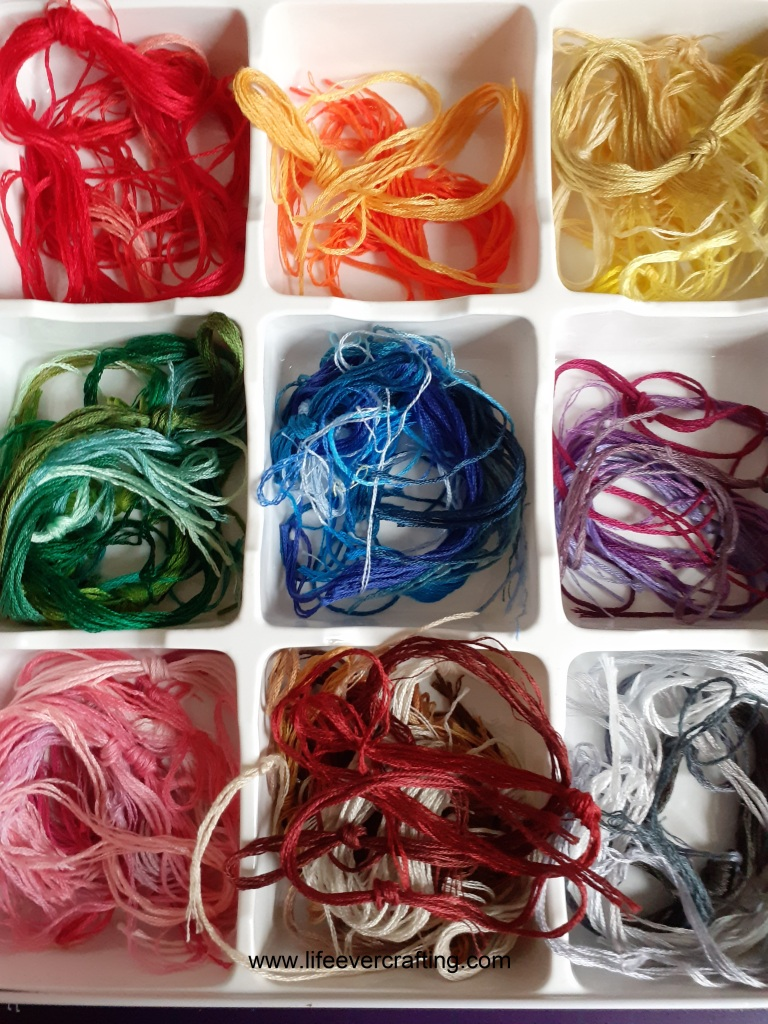 The image shows embroidery threads divided into rainbow colours in nine sections: red, orange, yellow, green, blue, purple. pink, brown, grey.