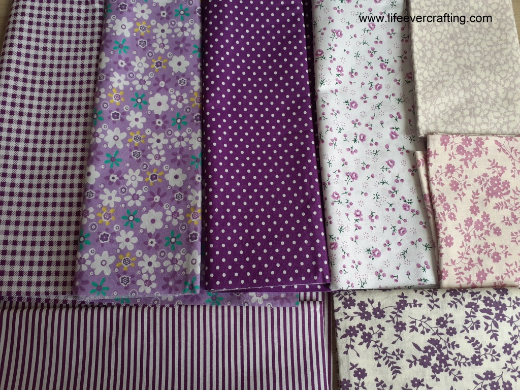 The image shows eight purple fat quarters with different patterns: five with flowers, one with polka dots, one gingham, and one striped.